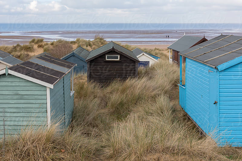 Several beach huts in sand dunes looking towards the sea by Paul Phillips for Stocksy United