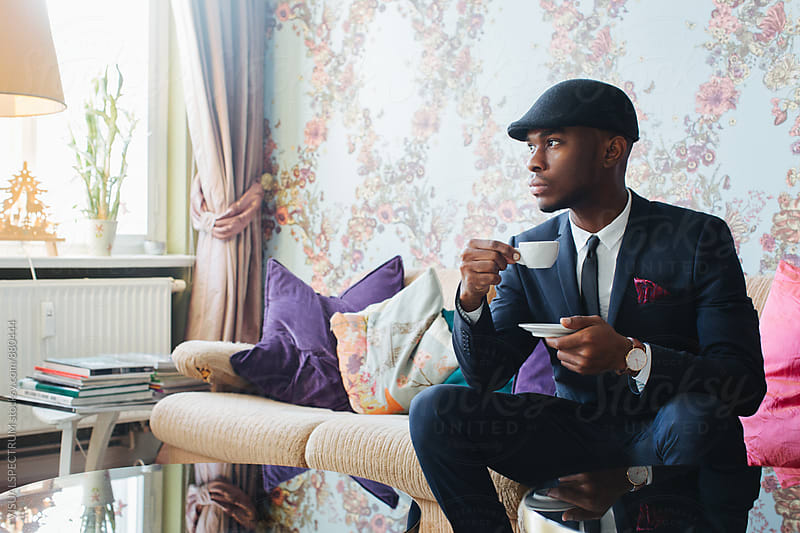 Stylish Young Black Man Sitting in Bright Living Room and Drinking Espresso by VISUALSPECTRUM for Stocksy United