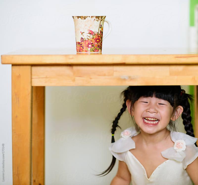 Little girl hidden herself under the table by Lawren Lu for Stocksy United