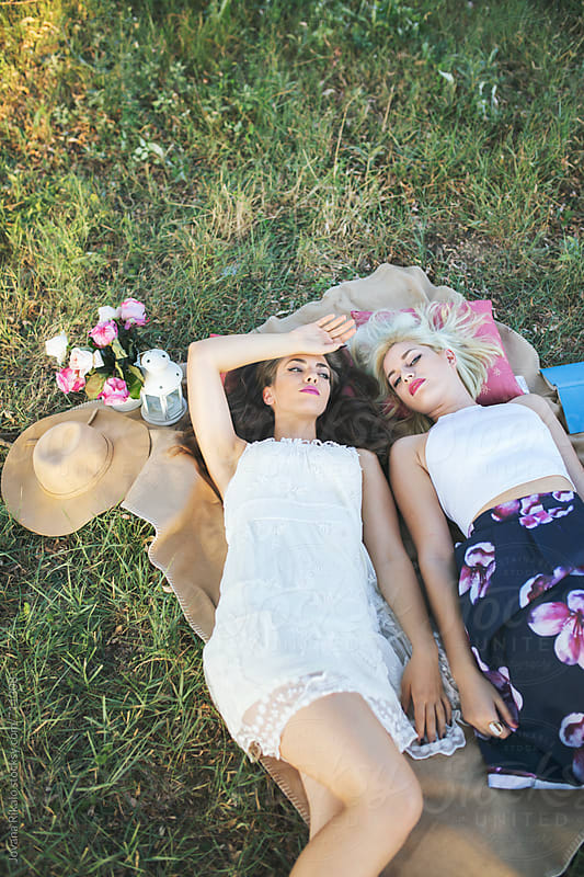 Two fashionable young women lying on a grass in a beautiful floral dresses by Jovana Rikalo for Stocksy United