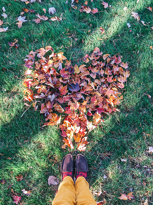 Autumn leaf love with woman's feet. by Holly Clark for Stocksy United