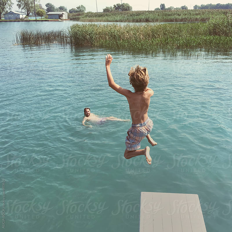 A Boy Happily Jumping Off A Diving Board Into A Summer Lake While His Dad Watches From The Water by ALICIA BOCK for Stocksy United