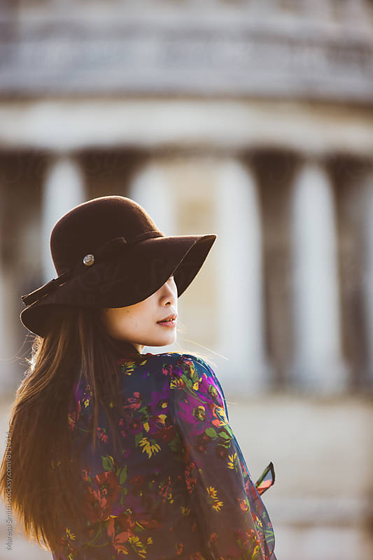 Profile of an asian girl wearing a floppy hat with a blurred building in the background by Maresa Smith for Stocksy United