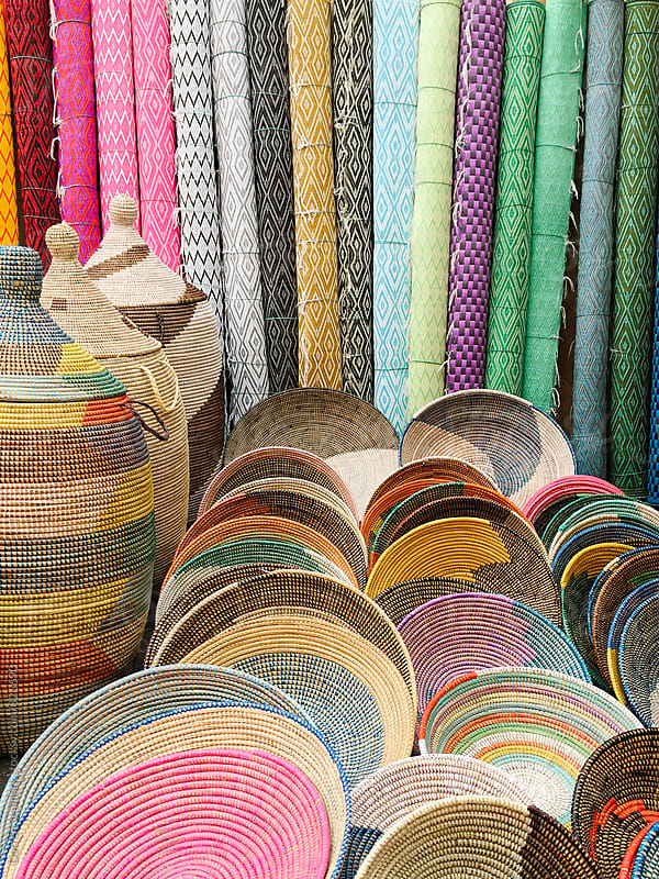 Multi-coloured fabric and baskets at a market by Darren Seamark for Stocksy United