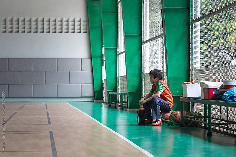 A young boy as a silent spectator in the sidelines. by Lawrence del Mundo for Stocksy United