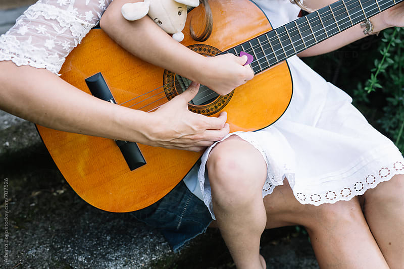 mother and daughter playing a guitar by Alberto Bogo for Stocksy United