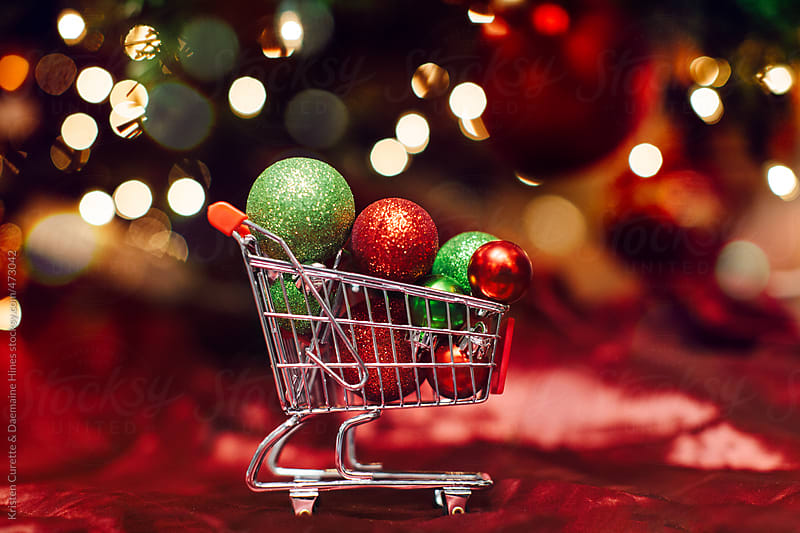 Christmas ornaments in a shopping cart under tree with lights by Kristen Curette Hines for Stocksy United