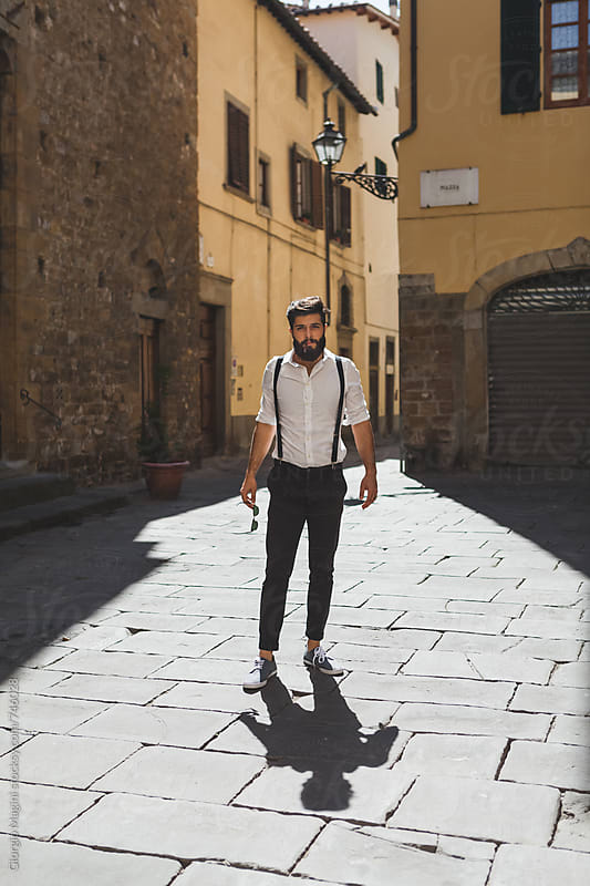 Fashionable Young Man Standing in an Old Italian Town by Giorgio Magini for Stocksy United