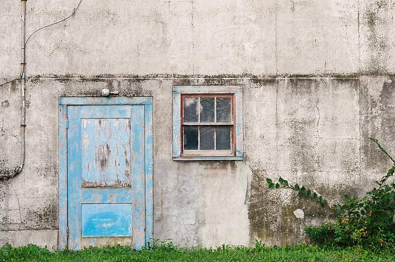 crumbling cement wall with blue door and window by Deirdre Malfatto for Stocksy United
