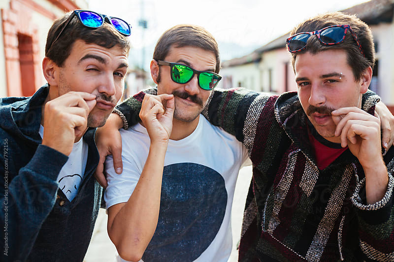 Three young happy friends together in a street of a traditional local village playing to be seductive curling their mustaches in a flirty way by Alejandro Moreno de Carlos for Stocksy United
