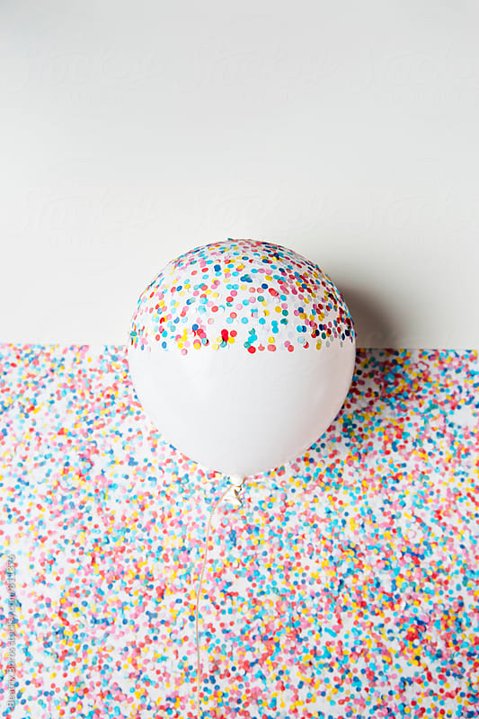 Balloon half covered with confetti by Beatrix Boros for Stocksy United