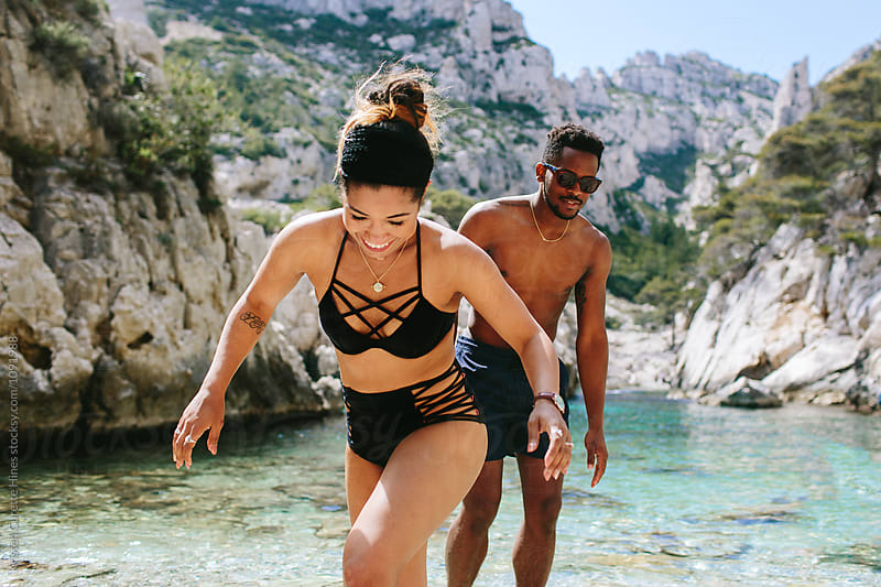 A man & a woman enjoying their summer vacation. They are in swim wear & by the ocean water.  by Kristen Curette Hines for Stocksy United