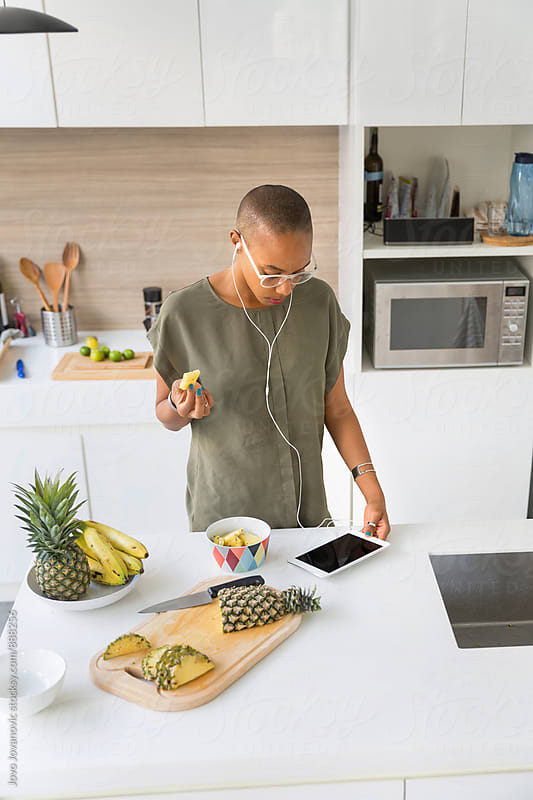 Smiling black woman using tablet in modern kitchen interior by Jovo Jovanovic for Stocksy United