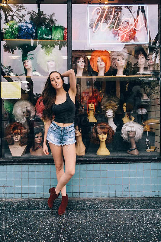 Young Woman Standing in Front of Wig Shop by Jayme Burrows for Stocksy United