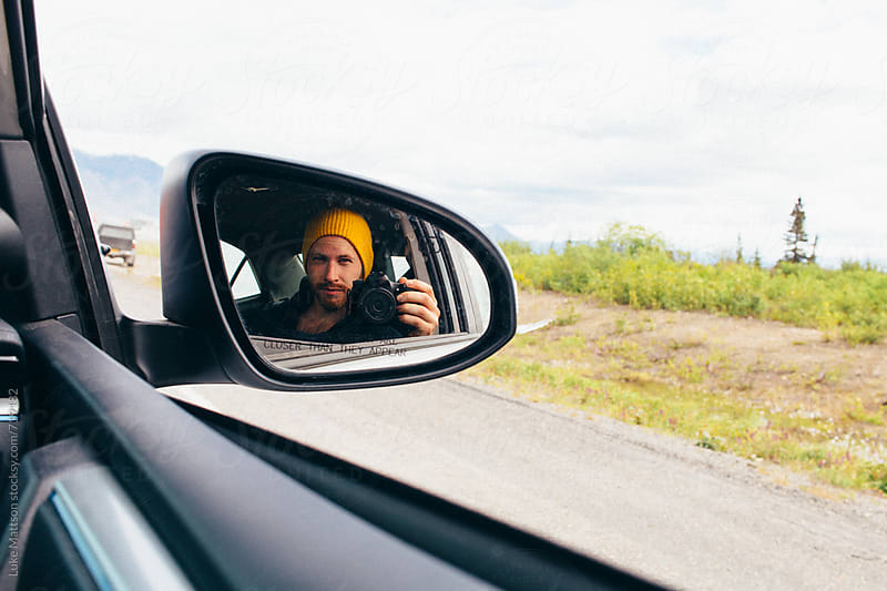 A Young Man Wearing A Yellow Beanie Takes A Selfie With His Camera In The Passenger Side Car Door Mirror by Luke Mattson for Stocksy United