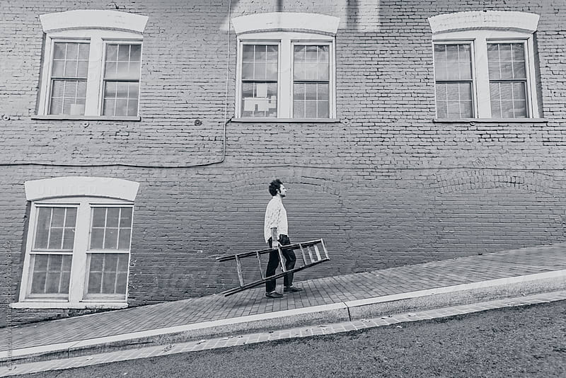 Man Carrying A Ladder Up A Steep Hill  by Cameron Whitman for Stocksy United