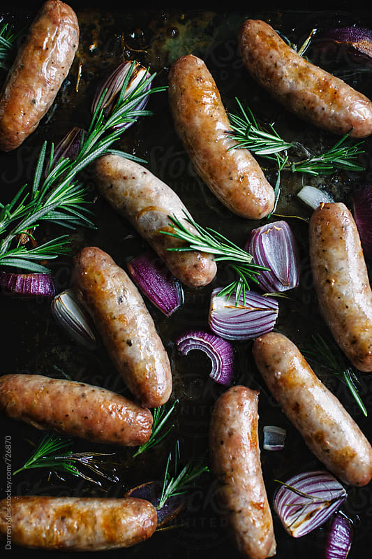 Tray of cooked sausages with red onion and rosemary.  by Darren Muir for Stocksy United