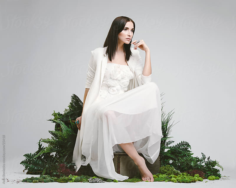 A beautiful brunette sitting in a studio in a wedding dress and  by Ania Boniecka for Stocksy United