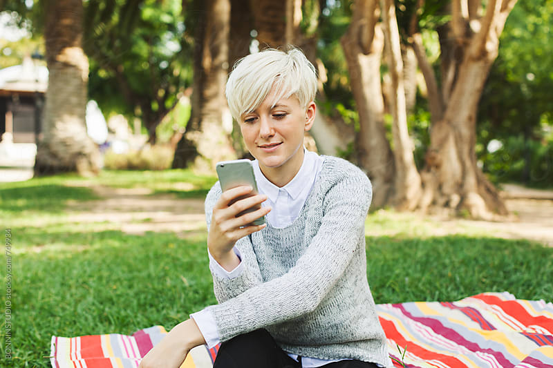 Blonde woman texting on her phone in the park. by BONNINSTUDIO for Stocksy United