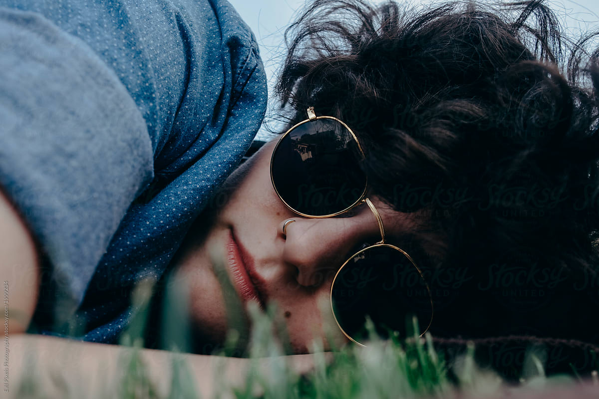 Stock Photo - Close Up Of A Tomboy Female Model With Sunglasses Lying On  The Grass