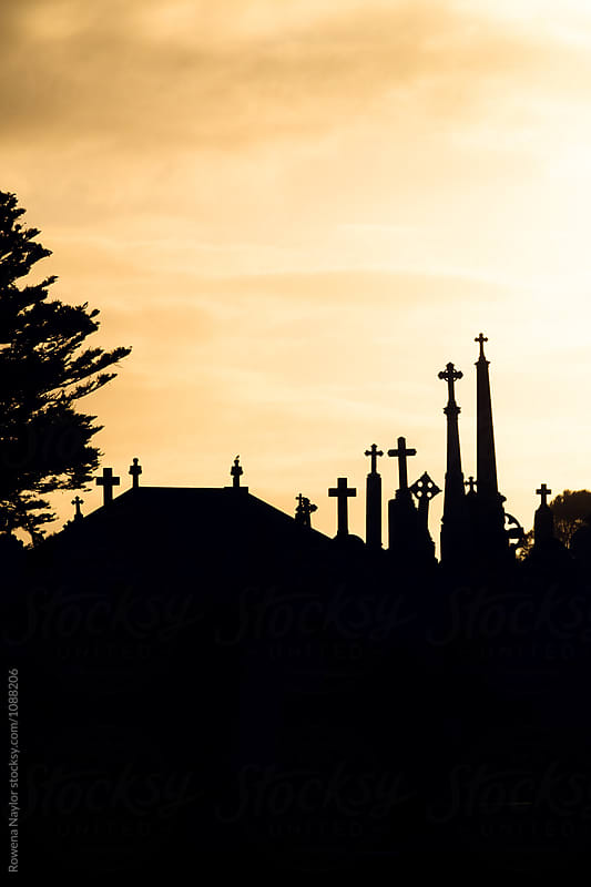 Silouette of catholic gravestones in cemetery by Rowena Naylor for Stocksy United