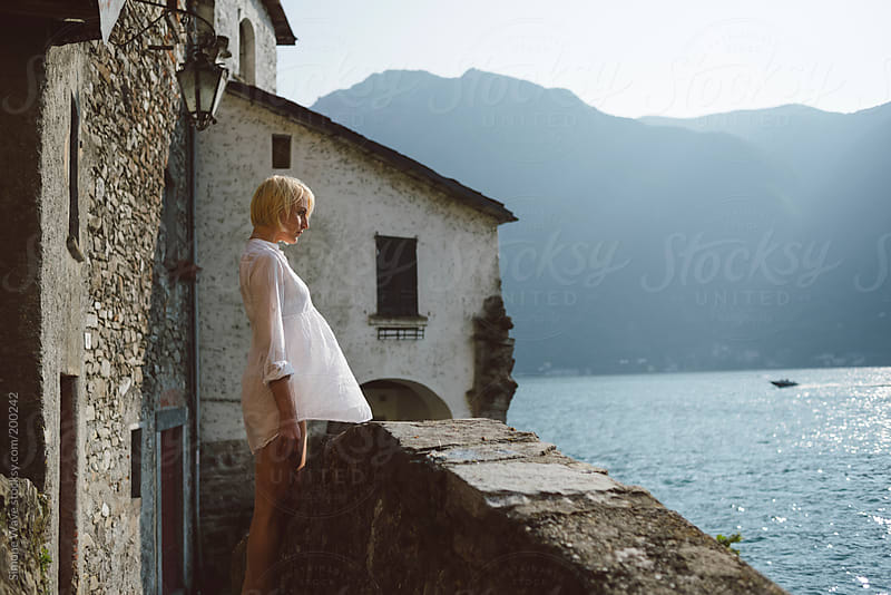 Young blonde woman relaxing across the lake by GIC for Stocksy United