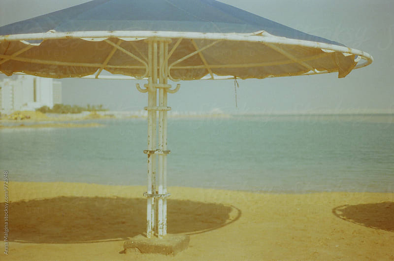 A film photo of umbrella on Dead Sea beach by Anna Malgina for Stocksy United