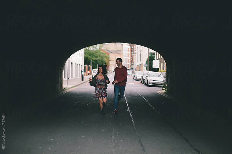 Couple Running Free in the Middle of the Street by HEX. for Stocksy United