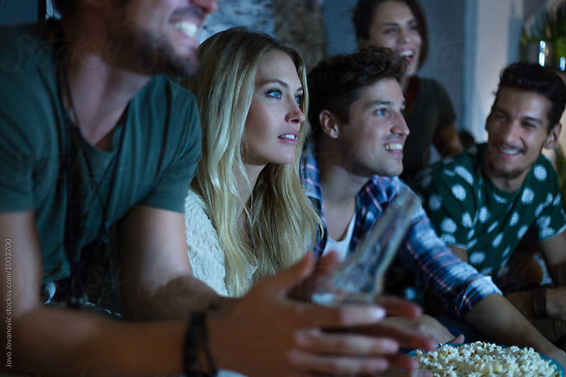 Group of friends watching tv together by Jovo Jovanovic for Stocksy United