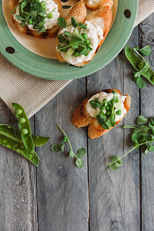 Ricotta and pea crostini. by Helen Rushbrook for Stocksy United