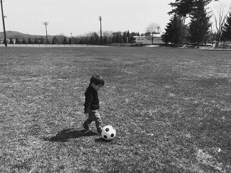 a toddler play football on the pitch by jira Saki for Stocksy United