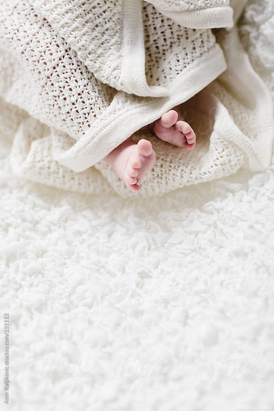 Bare pink feet of a tiny newborn baby by Amir Kaljikovic for Stocksy United