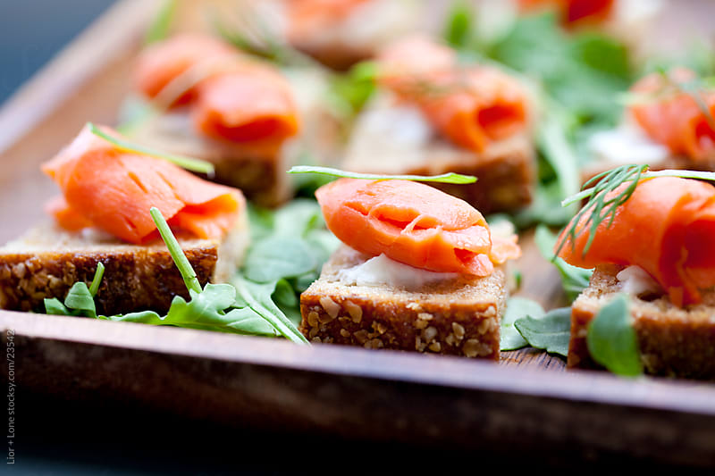 Smoked salmon canapes on a tray by Lior + Lone for Stocksy United