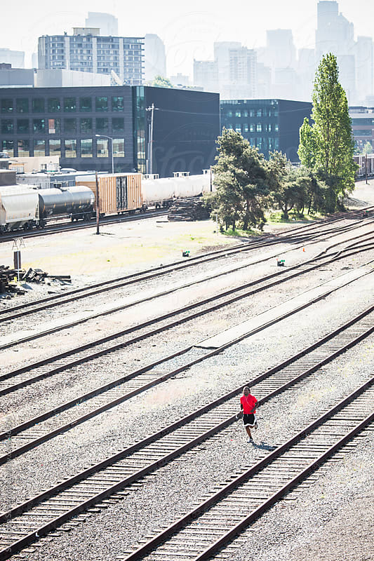 Male athlete running in an urban area next to railroads by Suprijono Suharjoto for Stocksy United