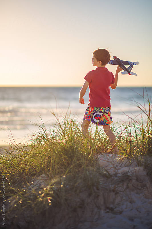Boy flying a toy plane at the beach by Angela Lumsden for Stocksy United