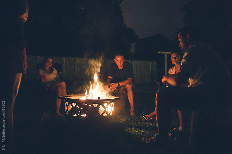 Authentic Conversation Among Friends Around Backyard Campfire by Brian McEntire for Stocksy United