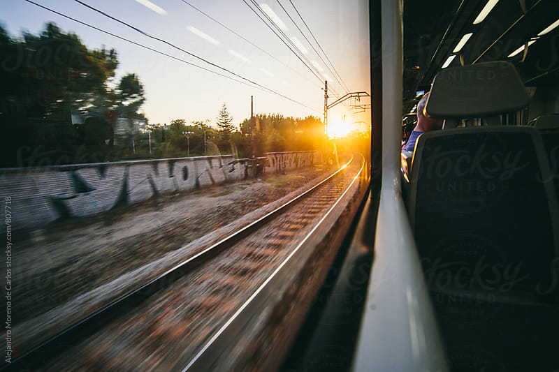 View of the sunset on the train track from a window seat moving fast by Alejandro Moreno de Carlos for Stocksy United