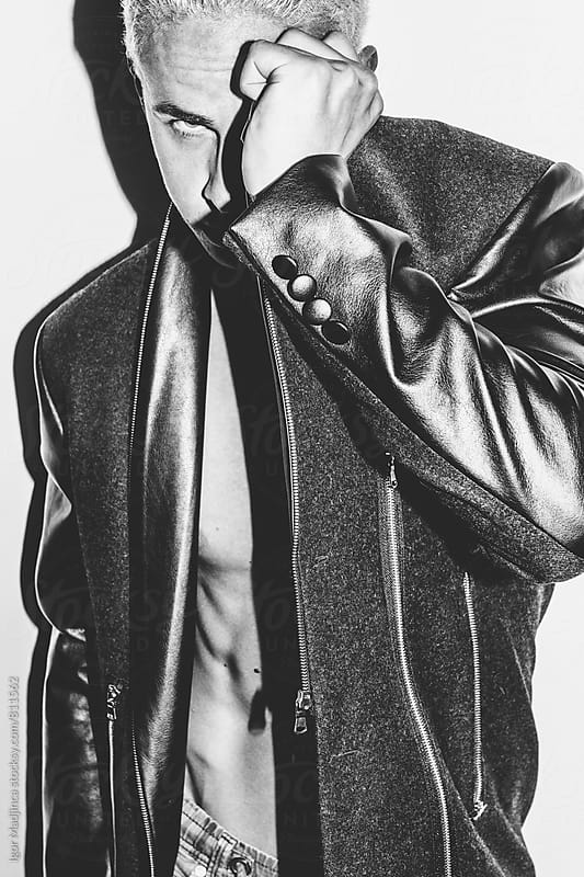 fashionable blond guy hiding his face in stylish leather jacket in front of a white wall by Igor Madjinca for Stocksy United
