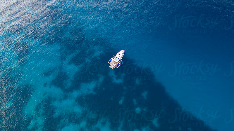 Beautiful aerial view of a coastline with a yacht by Song Heming for Stocksy United
