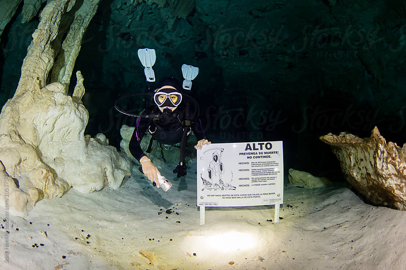A scuba diver pointing  Death warning board in Mexico's  Cenote Gran by Song Heming for Stocksy United