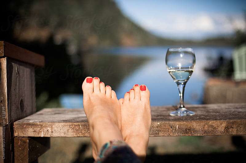Women's feet rest on a bench with a glass of wine as she looks towards the lake. by Cherish Bryck for Stocksy United