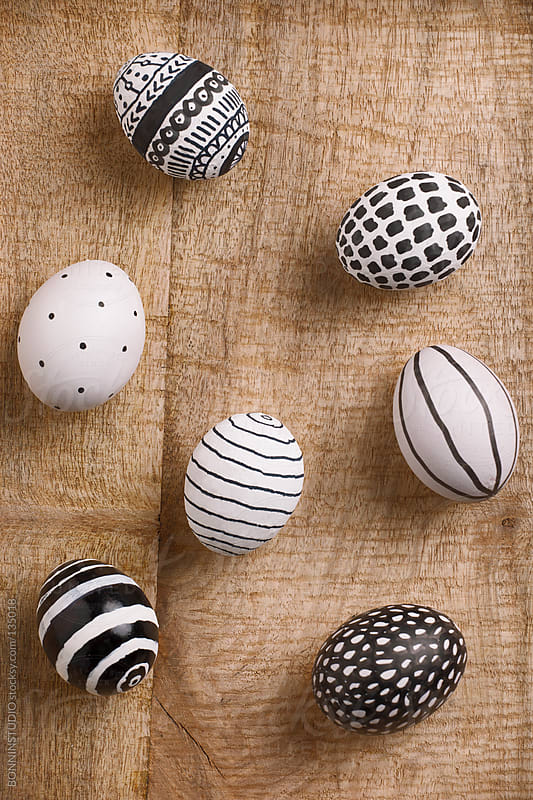 Easter eggs with different drawings on a wood background. by BONNINSTUDIO for Stocksy United