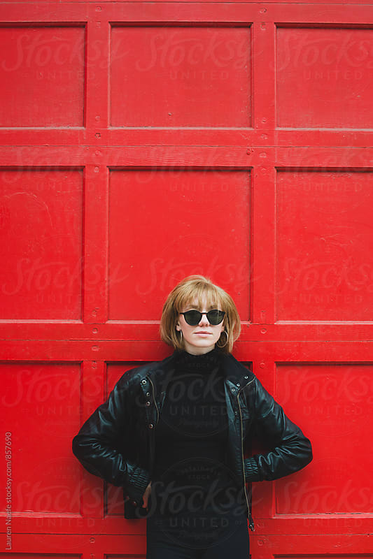 Cool young woman standing against red wall by Lauren Naefe for Stocksy United