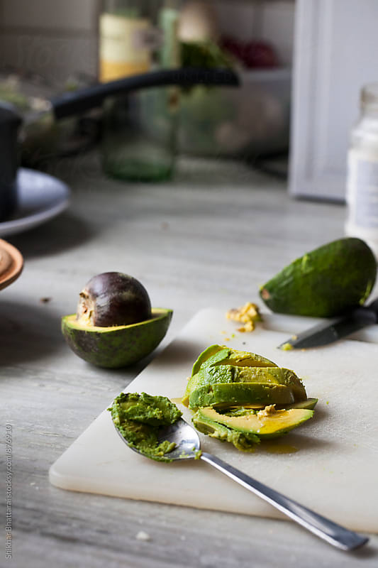Sliced avocado on a chopping board. by Shikhar Bhattarai for Stocksy United