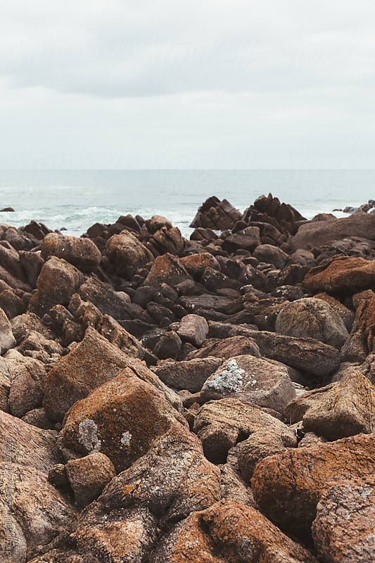 A view to the ocean over large rocks on the coastline by Jacqui Miller for Stocksy United