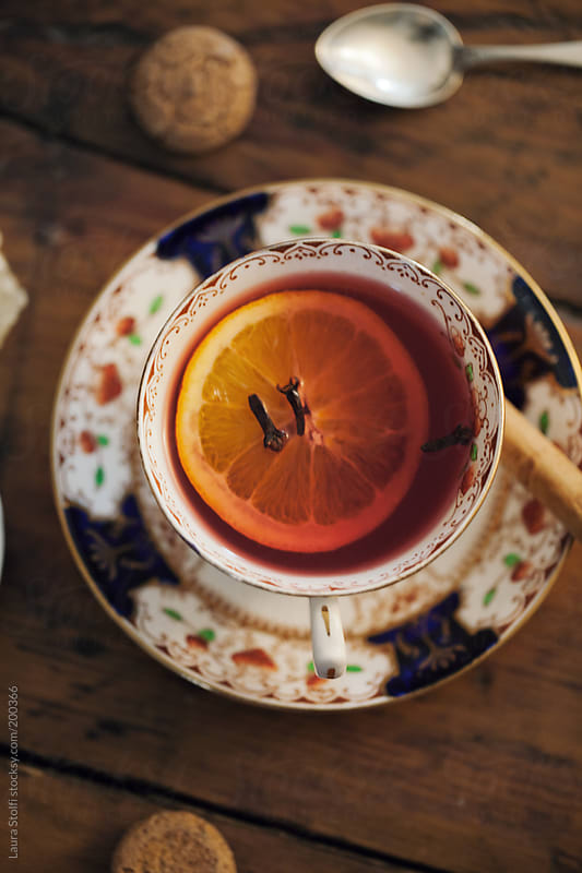 Wintry tea with cinnamon stick,  lemon slice, cloves and Amaretti cookies by Laura Stolfi for Stocksy United