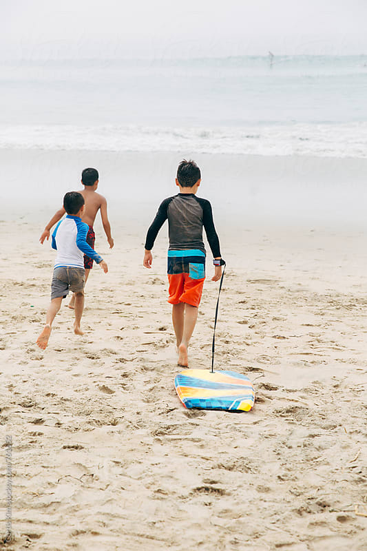 3 boys heading out into the surf at the ocean by Curtis Kim for Stocksy United