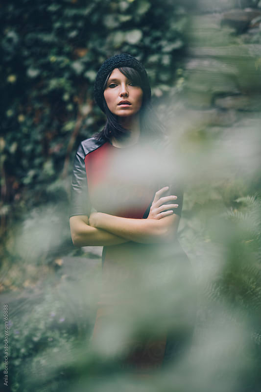 Stylish woman with arms crossed behind a blur of leaves by Ania Boniecka for Stocksy United