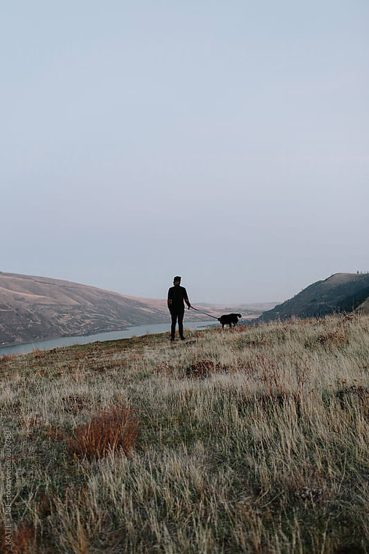 man standing in a filed overlooking a river with his dog by KATIE + JOE for Stocksy United