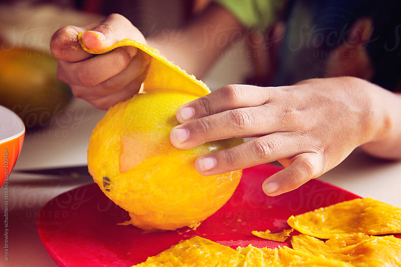 Close up of mango being peeled by anya brewley schultheiss for Stocksy United